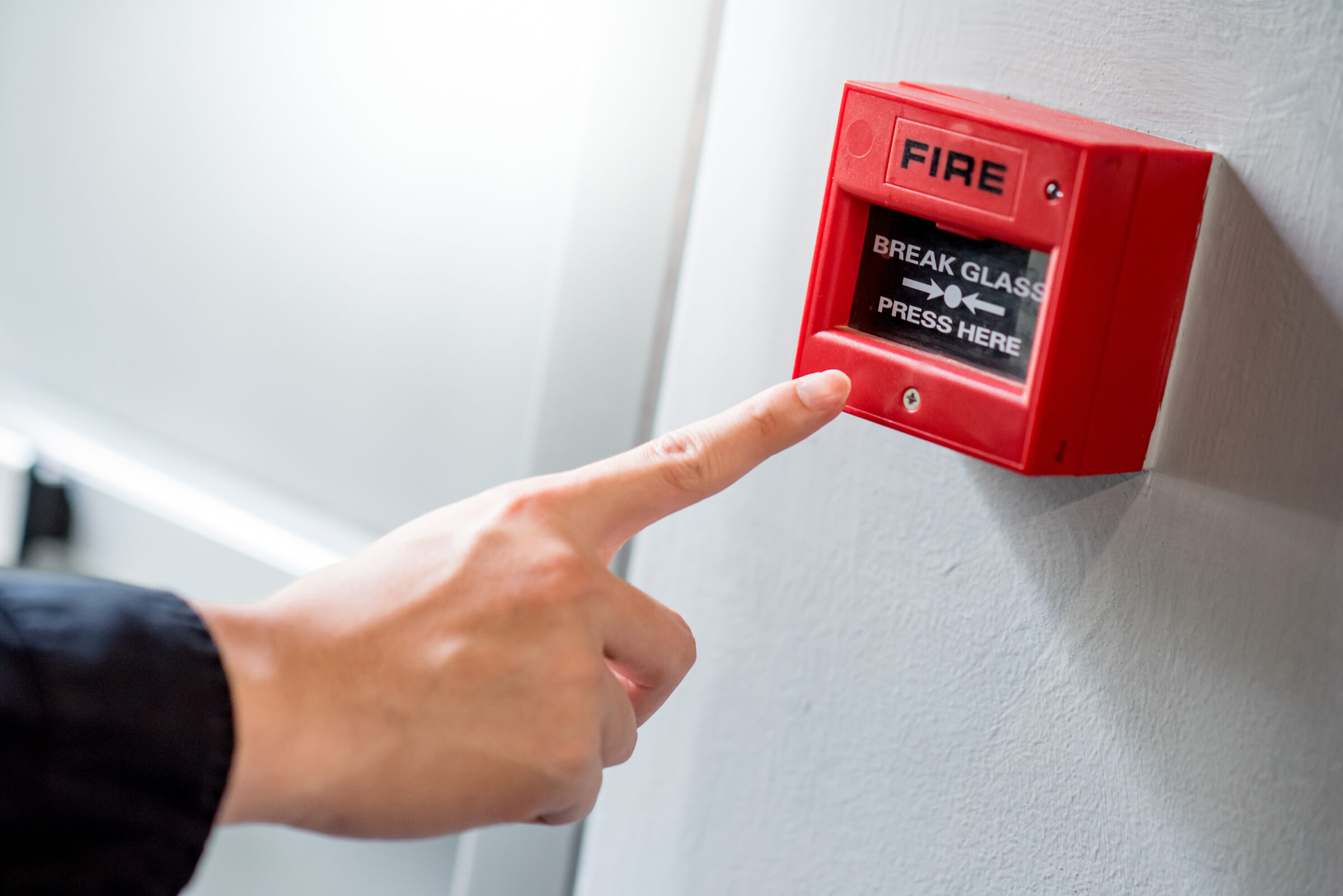 Male,Hand,Pointing,At,Red,Fire,Alarm,Switch,On,Concrete